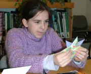 Origami proves to be more challenging than originally thought to one young library visitor engaged in a children's workshop supported by the Friends.